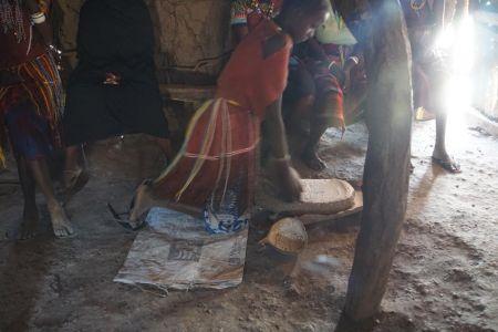 Datoga vrouw maalt mais voor Ugali