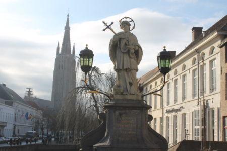 Heilig standbeeld met de Lieve-Vrouwe-Kerk op de achtergrond