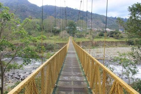 Gele hangbrug naar het dorp