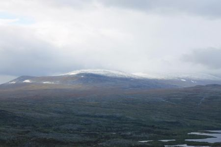 De wolken kruipen al over de bergtop